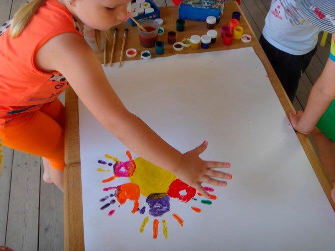 Заготовка ватмана, украшенная отпечатками ладоней детских рук